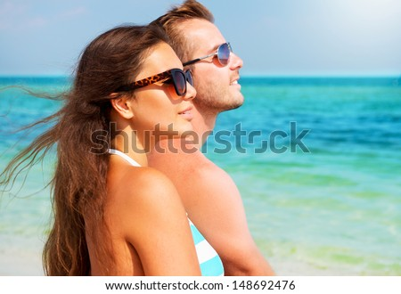 Happy Couple in Sunglasses having fun on the Beach. Summer Vacation. Laughing Family enjoying Nature over Sea Background. Attractive Man and Woman at the Beach  - stock photo
