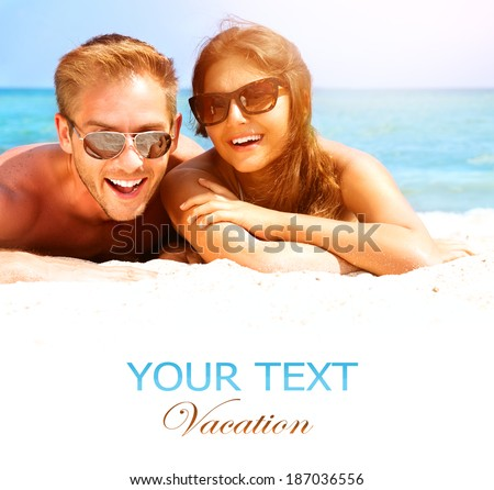 Happy Couple in Sunglasses having fun on the Beach. Summer Vacation. Laughing Family enjoying Nature over Sea Background. Attractive Man and Woman at the Beach. Sun tan - stock photo