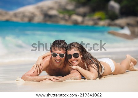 Happy Couple in Sunglasses having fun on the Beach. Summer Vacation. Laughing Family enjoying Nature over Sea Background. Attractive Man and Woman at the Beach. Sun tan. Maldives. Seychelles. - stock photo