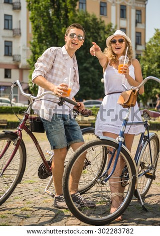 Happy couple in sunglasses with bicycles and glasses of juice on the city street. Woman pointing away. - stock photo