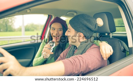 happy couple in the car. girlfriend is singing while man is driving. concept of happiness and carefree - stock photo