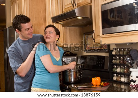 Happy couple in the kitchen. She is cooking on the stove near a counter and a chopped pepper. They are smiling as they look at each other happily. Horizontally framed photograph - stock photo