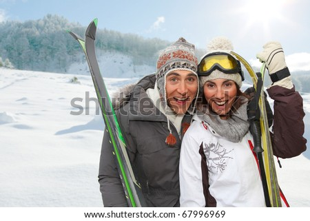 Happy couple in the mountains for ski vacation - stock photo