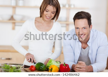 Happy couple in their Kitchen at home preparing vegetable salad - stock photo