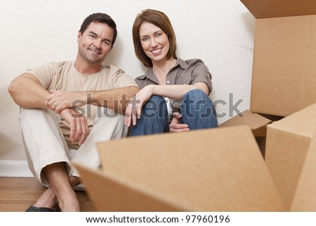 Happy couple in their thirties relaxing while unpacking or packing boxes and moving into a new home. - stock photo