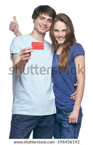 Happy couple in tshirts hugging, man showing blank credit card, woman gesturing thumb up, on white background