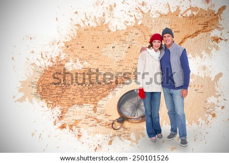 Happy couple in warm clothing against world map with compass showing north america - stock photo