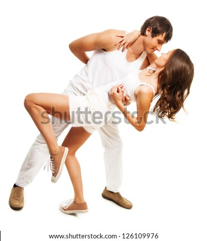 Happy couple in white clothes dancing together in intimate pose about to get kiss - stock photo