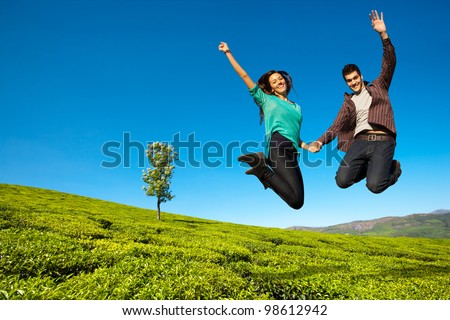 Happy couple jumping with hands raised in green field. - stock photo