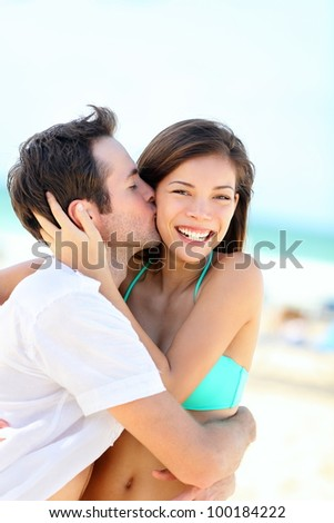 Happy couple kissing and embracing in joyful happiness showing love during summer beach vacation. Beautiful young interracial couple, Asian woman, Caucasian man outdoors. - stock photo