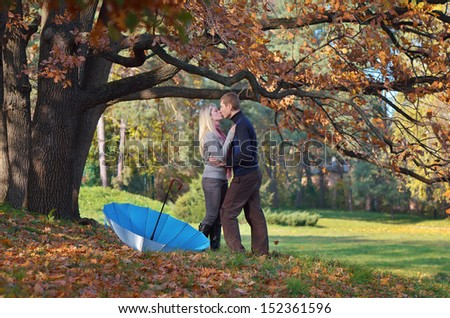 Happy couple kissing in autumn park under a tree - stock photo
