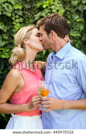 Happy couple kissing while toasting wineglasses at front yard - stock photo