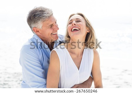 Happy couple laughing together at the beach - stock photo