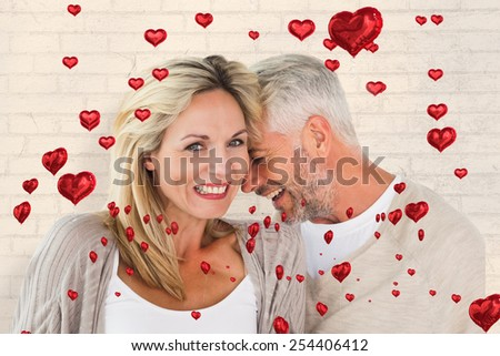 Happy couple laughing together woman looking at camera against white wall