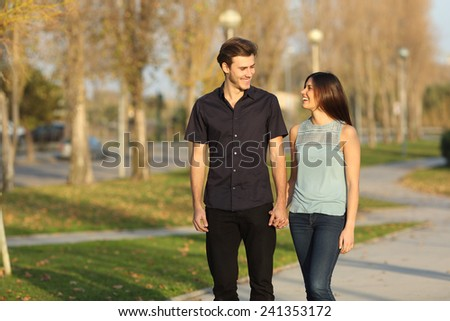 Happy couple laughing while taking a walk in a park - stock photo