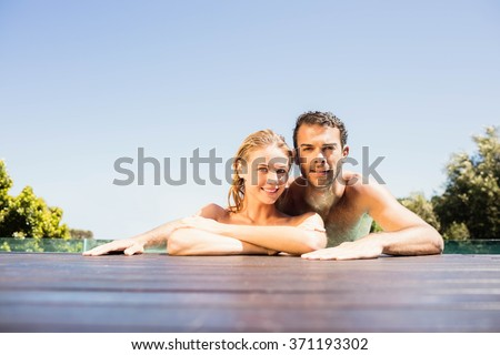 Happy couple leaning on pool edge and looking at the camera - stock photo