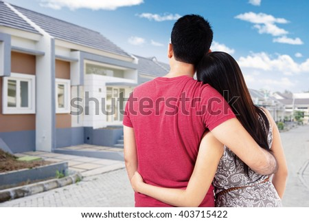 Happy couple look at a new residential construction while hugging each other - stock photo