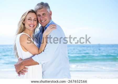 Happy couple looking at camera and hugging each other at the beach - stock photo