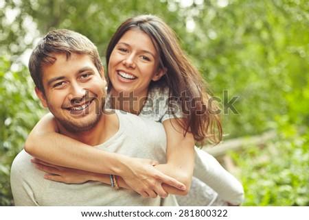 Happy couple looking at camera in natural environment - stock photo
