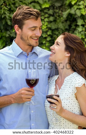 Happy couple looking at eachother while holding wineglasses at front yard