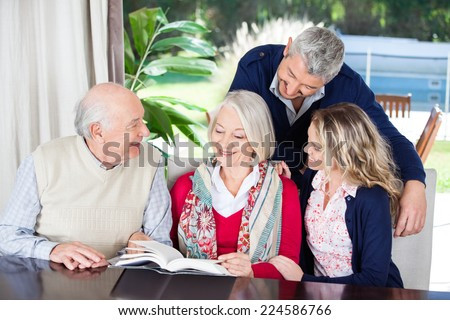 Happy couple looking at grandparents reading book while sitting in nursing home - stock photo