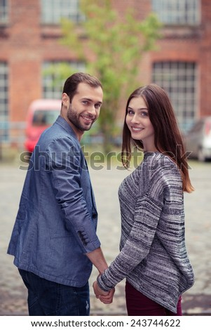 Happy couple looking back over their shoulders at the camera as they pause while walking hand in hand down a cobbled urban street - stock photo