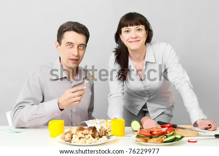 Happy couple looks at camera on kitchen - stock photo