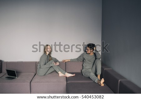 Happy couple lying down together in pigamas on sofa