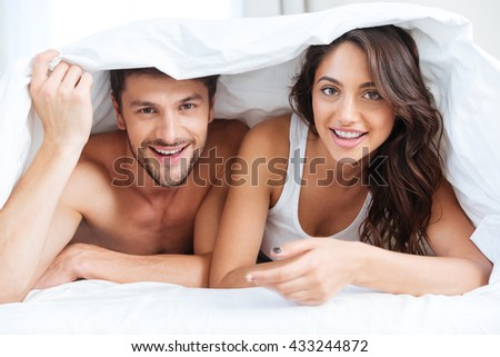 Happy couple lying in bed covered with blanket over head and talking at home over lights background at home - stock photo