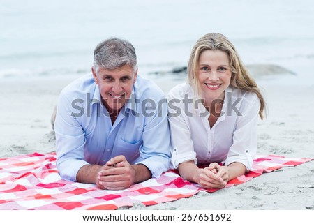 Happy couple lying on a blanket and smiling at camera at the beach - stock photo