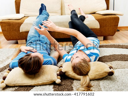 Happy couple lying on pillows on the floor