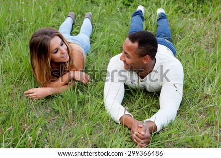 Happy couple lying on the grass in the field thinking about his future - stock photo