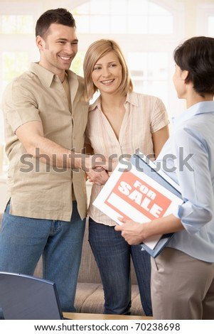 Happy couple making deal with estate agent, shaking hands.? - stock photo