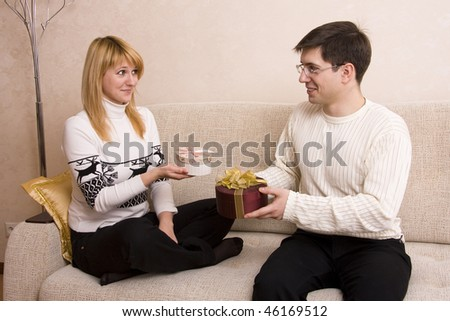 Happy couple. Man is giving gifts woman at Valentine?s day. Female congratulate  male at Christmas. - stock photo