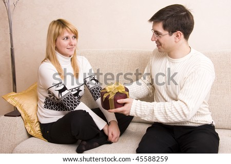 Happy couple. Man is giving gifts woman at Valentine?s day.  Male say happy birthday to female on white background. - stock photo