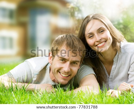 Happy Couple near their House.Smiling Family outdoor.Real Estate - stock photo