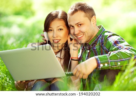 Happy couple of hipsters in trendy casual clothing using a laptop (with earphones) in park (forest, garden) and looking sweet and in love. Perfect shiny white smiles. Outdoor shot - stock photo