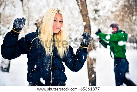 Happy couple of male and female embracing and having fun wearing warm clothes outside in winter park on snowdrift