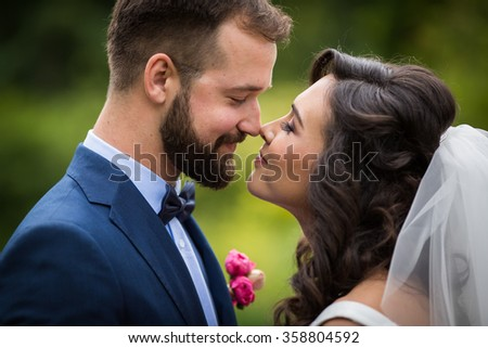 Happy couple of newlyweds looking at each other in a park closeup
