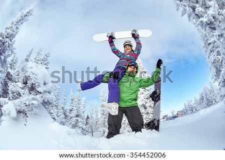 Happy couple of snowboarders having fun in winter forest at the top of Zelenaya mountain. Sheregesh resort, Siberia, Russia - stock photo