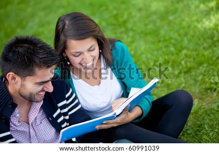 Happy couple of students with a notebook and smiling outdoors - stock photo