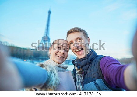 Happy couple of tourists having fun and taking selfie near the Eiffel tower in Paris