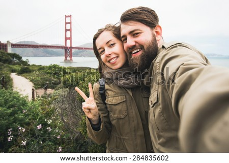 Happy couple of tourists in love laughing and making selfie photo with digital camera near Golden Gate Bridge in San Francisco, California, USA - stock photo