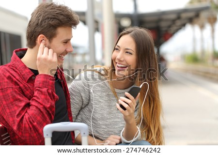 Happy couple of travelers sharing music on holidays during a travel in a train station - stock photo