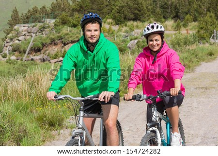 Happy couple on a bike ride wearing hooded jumpers in the countryside smiling at camera - stock photo