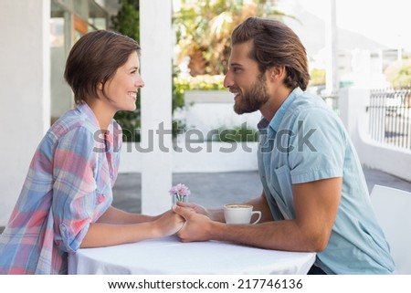 Happy couple on a date outside at the coffee shop - stock photo