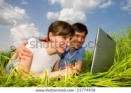 Happy couple on a laptop computer outdoors. Lay on the green grass. - stock photo
