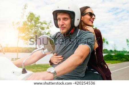 Happy couple on a motor bike - stock photo