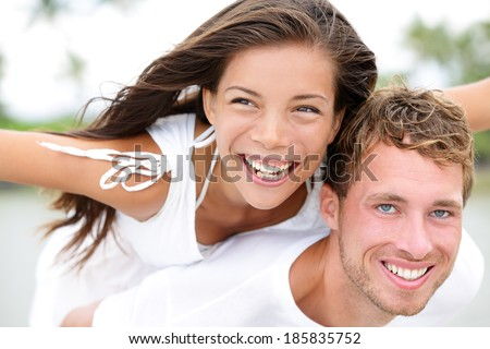 Happy couple on beach having fun piggyback ride in love outdoor smiling happy laughing together on romantic holidays vacation travel trip. Young multiracial people, Asian woman, Caucasian man, 20s. - stock photo