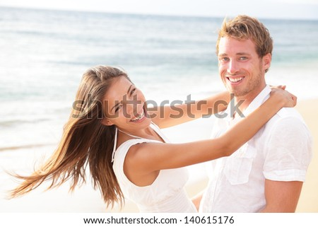 Happy couple on beach in love having fun holding around each other hugging looking at camera. Lifestyle portrait of healthy young interracial multi-ethnic newlywed couple on honeymoon. Asian woman. - stock photo